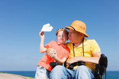 Disabled father and son playing with paper plane. Disabled father looking through binoculars with boy playing with paper plane royalty free stock images