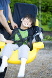 Disabled five year old boy in handicap swing. Disabled five year old boy getting strapped  into handicap swing Royalty Free Stock Photos