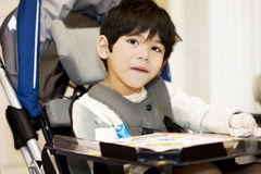 Disabled four year old boy studying. Or reading in wheelchair Stock Images