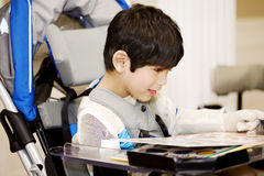 Disabled four year old boy studying  in wheelchair Royalty Free Stock Images