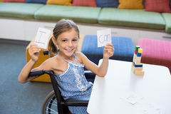 Disabled girl holding placard that reads I Can in library Stock Photography