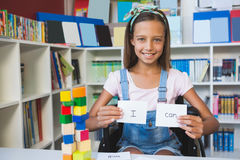Disabled girl showing placard that reads I Can in library Stock Images