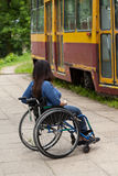 Disabled girl waiting for a tram. Vertical Stock Photography