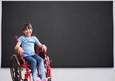 Disabled girl in wheelchair in front of blackboard royalty free stock images