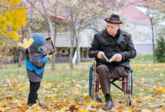 Disabled grandfather watching his grandson Royalty Free Stock Image