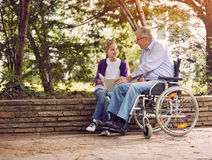 Disabled grandfather in wheelchair in park spending time togethe. R with his granddaughter reading book outdoor Stock Images