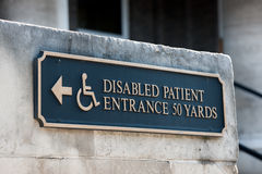 Disabled handicap entrance entrance sign. Disabled patient entrance tablet sign on a public stone wall in a capital city Stock Photography