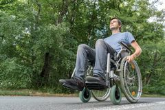 Disabled or handicapped young man is sitting on wheelchair in nature stock photo