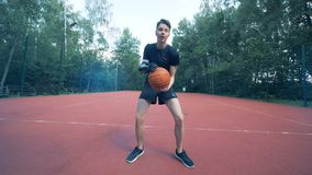 Disabled human cyborg with bionic prosthesis plays basketball with his artificial arm. 4K. A man plays basketball, throwing a ball into a basket