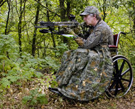 Disabled hunter. Handicapped hunter in a wheelchair with a crossbow in the woods Royalty Free Stock Photo