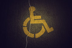 Disabled icon on broken asphalt Stock Photos