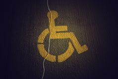 Disabled icon on broken asphalt Stock Photos