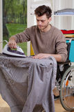 Disabled ironing shirts on board Stock Photography