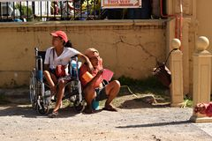 Disabled lady on wheelchair with other male beggars at church yard begging for alms. San Pablo City, Laguna, Philippines - March 25, 2018: Disabled lady on royalty free stock image