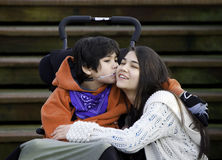 Disabled little boy kissing his big sister on cheek while seated Stock Photo