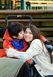 Disabled little boy kissing his big sister on cheek while seated Stock Photos