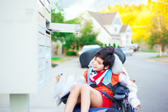 Disabled little boy in wheelchair getting mail from mailbox Royalty Free Stock Photography