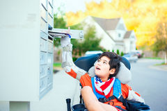 Disabled little boy in wheelchair getting mail from mailbox Stock Photos