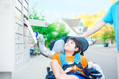Disabled little boy in wheelchair getting mail from mailbox Royalty Free Stock Photos