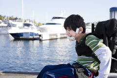 Disabled little boy in wheelchair out on pier by lake Royalty Free Stock Image