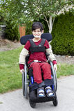 Disabled little boy in wheelchair outdoors Royalty Free Stock Photo