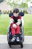 Disabled little boy in wheelchair outdoors Royalty Free Stock Photos