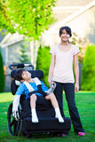 Disabled little boy in wheelchair with sister on grassy lawn out Royalty Free Stock Photos