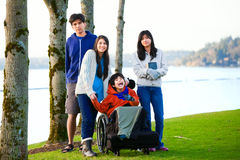 Disabled little boy in wheelchair surrounded by brother and sisters at lakeside. Child has cerebral palsy and children are all bi royalty free stock photography