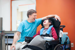 Disabled little boy in wheelchair talking with father in hospita Royalty Free Stock Photos