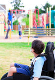Disabled little boy in wheelchair watching children play on play Stock Photo