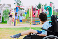 Disabled little boy in wheelchair watching children play on play. Disabled little boy in wheelchair sadly watching children play on playground Stock Photo
