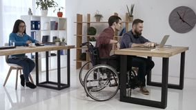 Disabled worker and colleagues working in office stock footage