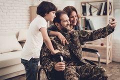 Disabled Male Soldier Is Making A Family Selfie. Disabled Man In A Wheelchair Makes A Selfie With Family. Meeting After War. Son And Wife. Camouflage Uniform stock photos