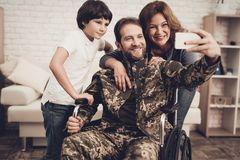 Disabled Male Soldier Is Making A Family Selfie. Disabled Man In A Wheelchair Makes A Selfie With Family. Meeting After War. Son And Wife. Camouflage Uniform royalty free stock images