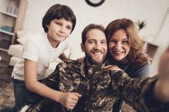 Disabled Male Soldier Is Making A Family Selfie. Disabled Man In A Wheelchair Makes A Selfie With Family. Meeting After War. Son And Wife. Camouflage Uniform royalty free stock photography