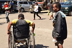Disabled male on wheelchair with other male beggars at church yard begging for alms. San Pablo City, Laguna, Philippines - March 25, 2018: Disabled male on stock image
