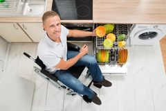 Disabled man arranging plate in dish rack Stock Photography