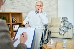 Disabled man in assisted living center. Crop therapist having meeting with disabled senior men in cozy room of assisted living center stock photography