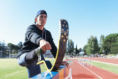 Disabled man athlete stretching with leg prosthesis. stock photos
