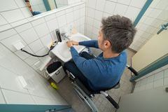 Disabled man in bathroom washing hands Stock Photo