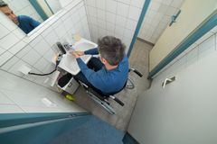 Disabled man in bathroom washing hands Stock Images
