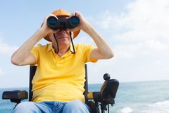 Disabled man with binocular. Disabled man with binocular sitting on the wheelchair. Sea on the background Stock Image