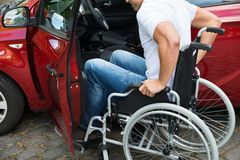 Disabled man boarding in his car. Close-up Of A Disabled Man In Wheelchair Getting In His Car Royalty Free Stock Photography