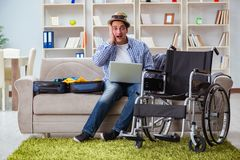 The disabled man booking travel online using laptop computer Stock Photo