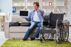 The disabled man booking travel online using laptop computer Stock Image