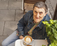 Disabled man with cerebral palsy sitting an  cafe. Royalty Free Stock Photo