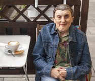 Disabled man with cerebral palsy sitting at outdoor cafe. Royalty Free Stock Image