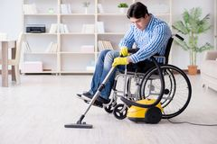 The disabled man cleaning home with vacuum cleaner Royalty Free Stock Image