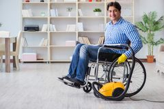 The disabled man cleaning home with vacuum cleaner Royalty Free Stock Images