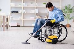 The disabled man cleaning home with vacuum cleaner. Disabled man cleaning home with vacuum cleaner Royalty Free Stock Photos
